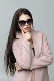 Le portrait d'une fille s'est habillé dans un manteau et des lunettes de soleil sur un b nu Photographie stock