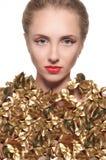 Le portrait d'une fille s'est habillé dans une feuille d'or sur le fond blanc Photos libres de droits