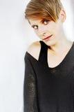 Le portrait d'une jeune femme dans le noir a tricoté le chandail Image stock