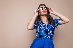 Le portrait d'une jeune femme joyeuse s'est habillé dans la robe bleue et des lunettes de soleil regardant l'appareil-photo d'iso images stock