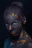 Le portrait d'une jeune femme qui pose a couvert de peinture noire images libres de droits