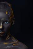 Le portrait d'une jeune femme qui pose a couvert de peinture noire image libre de droits