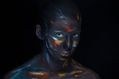 Le portrait d'une jeune femme qui pose a couvert de peinture noire image stock