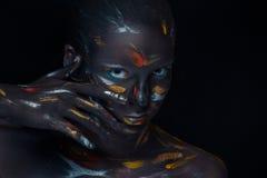 Le portrait d'une jeune femme qui pose a couvert de peinture noire images stock