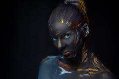 Le portrait d'une jeune femme qui pose a couvert de peinture noire photographie stock