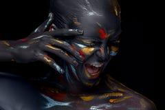Le portrait d'une jeune femme qui pose a couvert de peinture noire photo libre de droits