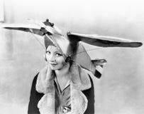 Le portrait d'une jeune femme utilisant un avion a formé le chapeau (toutes les personnes représentées ne sont pas plus long viva Photos stock