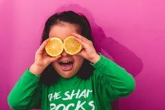 Le portrait d'une jeune fille tenant deux a coupé en tranches des citrons dans ses yeux photographie stock