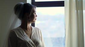 Le portrait d'une jeune mariée, belle fille, dans le voile et le peignoir blanc, robe longue, regarde la fenêtre clips vidéos