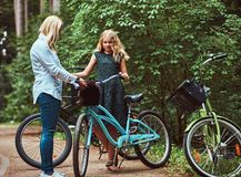 Le portrait d'une mère et la fille avec des cheveux blonds sur une bicyclette montent avec leur petit chien mignon de spitz en pa Images libres de droits