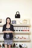 Le portrait d'une mi femme adulte se tenant avec des bras a croisé dans le magasin de chaussures Image libre de droits