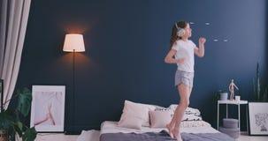 Le portrait d'une petite fille ?coutant la musique avec les ?couteurs et dansant sur ses parents enfoncent Concept : Musique banque de vidéos