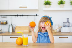 Le portrait d'une petite fille dans une robe bleue joue avec des oranges sur une table photos libres de droits