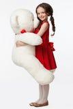 Le portrait d'une petite fille de brune dans une robe rouge avec un doux soit Photos stock