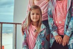 Le portrait d'une petite fille mignonne avec les cheveux blonds s'est habillé dans un T-shirt rose et un hoodie bleu se tenant av images stock
