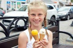 Le portrait de 7 années badinent la fille mangeant la crème glacée savoureuse dans la ville Photo libre de droits