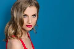 Le portrait de beauté de la jeune femme blonde avec les lèvres rouges lumineuses, yeux bleus, dans la robe rouge sur le fond bleu photo libre de droits