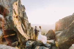 Le portrait de beaux couples de nouveaux mariés dans le coucher du soleil s'allume sur le paysage majestueux de montagne avec de  Image libre de droits