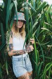 Le portrait de beaux jeunes a tatoué la femme de sourire se tenant dans le buisson feuillu vert Images libres de droits