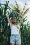 Le portrait de beaux jeunes a tatoué la femme de sourire se tenant dans le buisson feuillu vert Photos stock