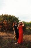 Le portrait de belles jeunes filles s'est habillé dans l'ornoe et long rouge Photographie stock