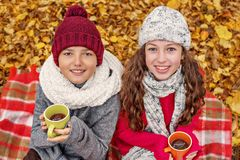 Le portrait de deux adolescents dans une fille confortable de chapeau et d'écharpe et le garçon worm par le thé des tasses Photo stock