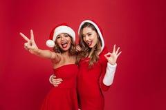 Le portrait de deux a excité les filles espiègles dans des robes de Noël Image stock