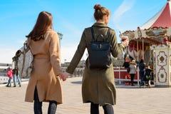 Le portrait de deux femmes avec le dos, descendent la rue dans les manteaux et des sacs à dos et tiennent des mains Photographie stock