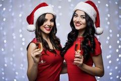 Le portrait de deux femmes dans des chapeaux de Santa et la robe rouge avec le champagne dans des mains sur le bokeh allument le  Photographie stock