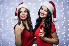 Le portrait de deux femmes dans des chapeaux de Santa et la robe rouge avec le champagne dans des mains sur le bokeh allument le  Photo stock