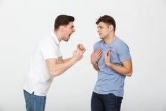 Le portrait de deux a frustré des jeunes hommes ayant un argument images stock