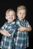 Le portrait de deux garçons mignons tenant des bras a plié des expressions drôles Photographie stock