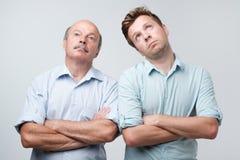 Le portrait de deux hommes avec ennuyé alimenté vers le haut de l'expression, regards a contrarié, étant fatigué pour expliquer l images stock