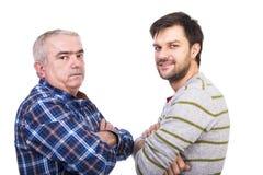 Le portrait de deux hommes, père et fils, se tenant avec des bras a plié a Images libres de droits