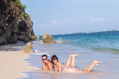 Le portrait de deux jeunes amis féminins se trouvent sur le bord de mer regardant l'appareil-photo et rire Jeunes femmes caucasie Photographie stock
