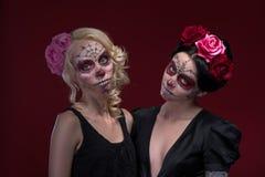 Le portrait de deux jeunes filles dans le noir s'habille avec Photos stock