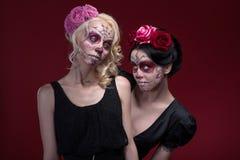 Le portrait de deux jeunes filles dans le noir s'habille avec Images stock