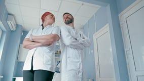 Le portrait de deux médecins sûrs avec des bras a plié la position dans la chambre d'hôpital banque de vidéos