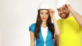 Le portrait de deux ports gais d'ingénieurs ou d'architectes a eu la position de chapeaux sur le fond blanc image stock