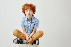 Le portrait de a ennuyé peu d'enfant avec les cheveux rouges et les taches de rousseur se reposant sur la boîte avec l'expression photos stock