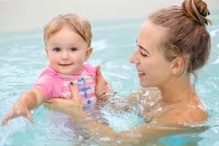 Le portrait de groupe de la fille caucasienne blanche de mère et de bébé jouant dans la plongée de l'eau dans la piscine à l'inté Photographie stock libre de droits