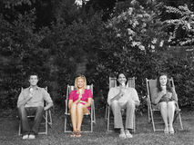 Le portrait de jeunes amis heureux s'asseyant sur la chaise de plate-forme avec le crème dans l'arrière-cour Photo stock