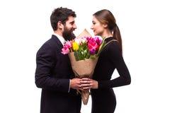 Le portrait de jeunes couples dans l'amour avec le bouquet de la pose de tulipes de ressort s'est habillé dans des vêtements clas Images stock