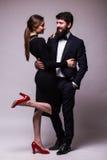 Le portrait de jeunes couples dans la pose d'amour s'est habillé dans des vêtements classiques sur le backround gris Homme avec l Photos stock