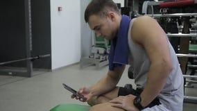 Le portrait de jeunes sportifs caucasiens qui se repose dans le gymnase mettant en rouleau l'écran de son téléphone portable banque de vidéos