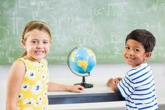 Le portrait de l'école heureuse badine la position dans la salle de classe images libres de droits