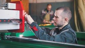 Le portrait de l'électricien sur des combinaisons fonctionne avec le panneau d'énergie et l'équipement de machines sur l'usine photographie stock libre de droits