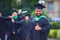 Le portrait de l'étudiant indien réussi dans la robe d'obtention du diplôme manient maladroitement  images stock