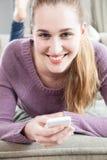 Le portrait de l'adolescente magnifique heureuse s'est relié à son smartphone Photos stock