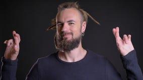 Le portrait de l'apparence caucasienne charismatique d'homme a croisé des doigts signent pour montrer l'espoir sur le fond noir banque de vidéos